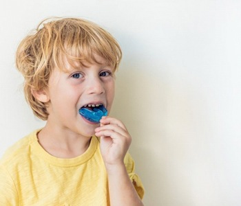 little boy inserting mouthguard