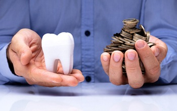 An individual holding a model tooth in one hand and a handful of change in the other