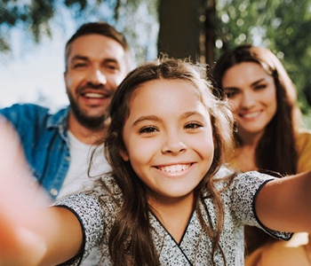 child taking a selfie with their parents