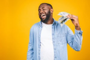 man holding money for CareCredit for cosmetic dental treatment