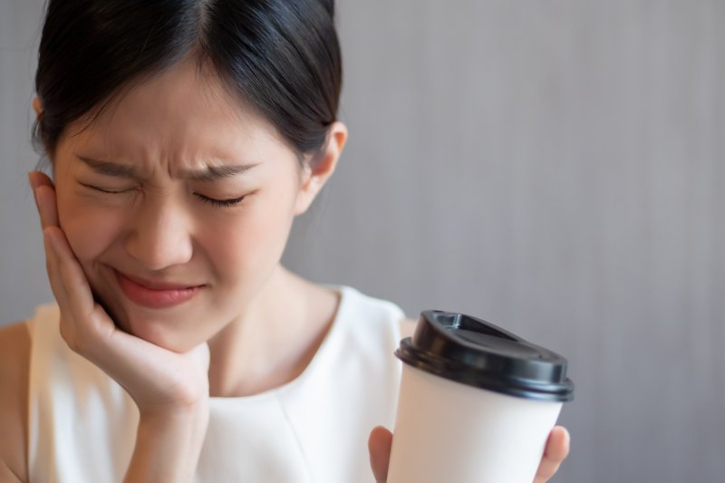Woman experiencing tooth sensitivity from morning coffee