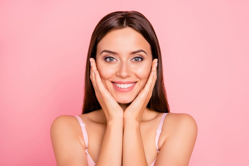 Closeup of woman smiling with veneers against pink background