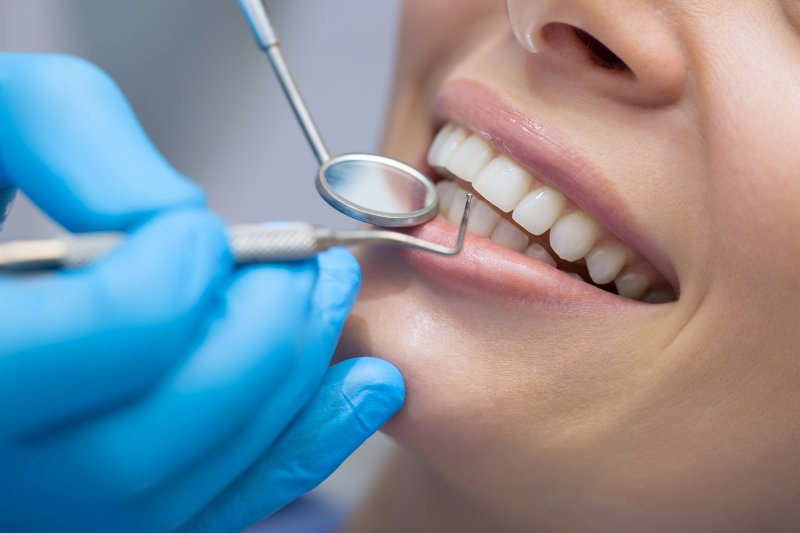 Dentist using dental tools to examine patient's teeth