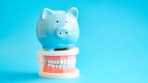 light blue piggy bank sitting on top of a set of dentures